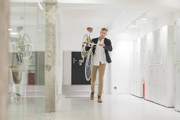 geschäftsmann, tragen seine fahrrad im büro - fahrradträger stock-fotos und bilder