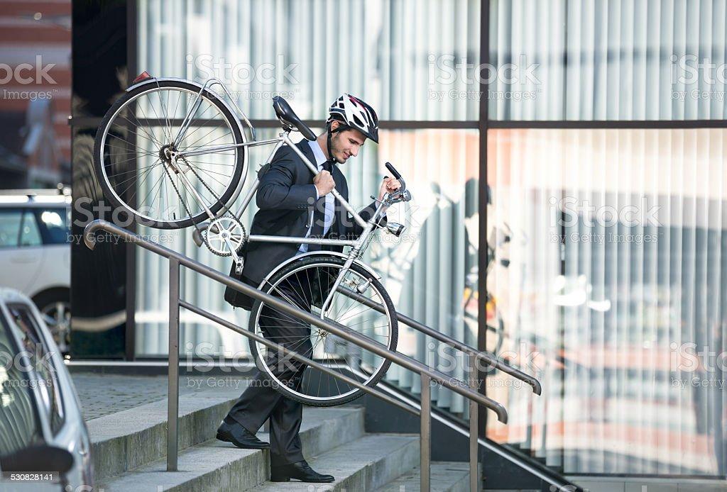 businessman carrying his bike stock photo