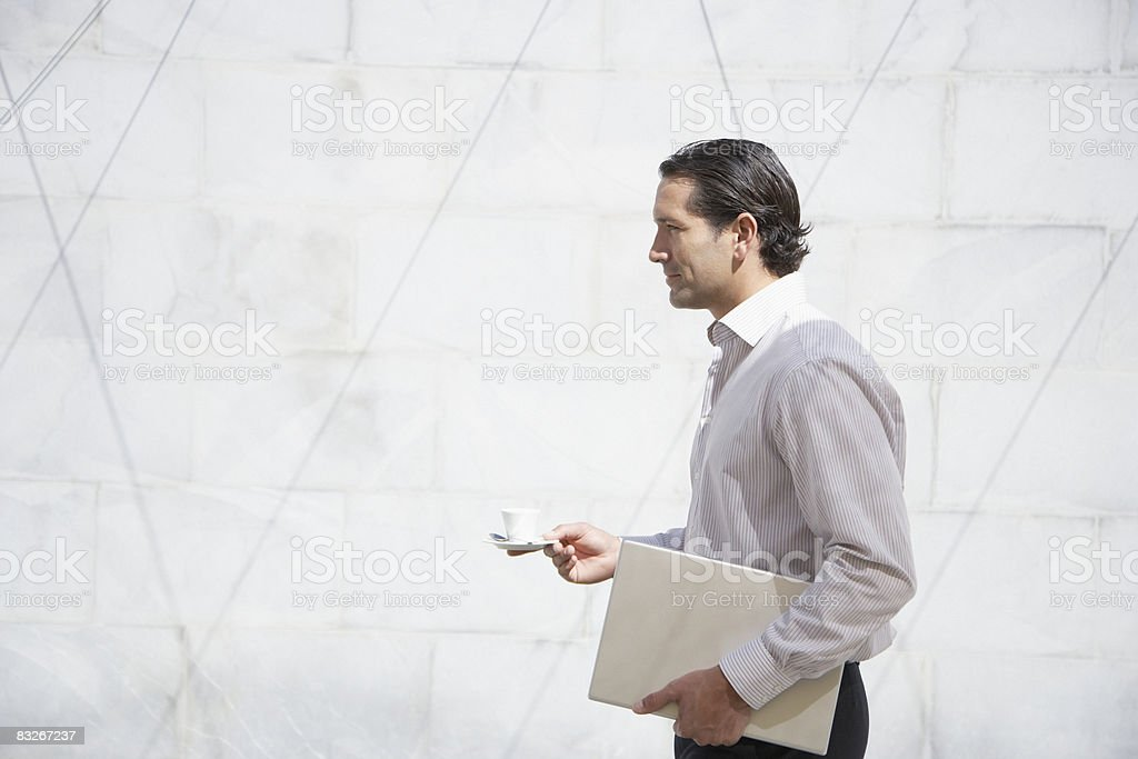 Businessman carrying laptop and cup of coffee royalty free stockfoto