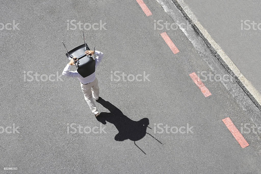 Businessman carrying office chair in roadway stock photo