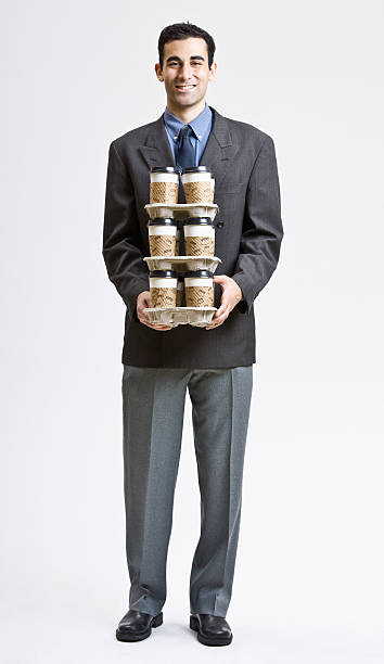 Businessman Carrying Stack of Coffee Cups stock photo