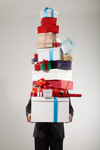 Businessman carrying stack of christmas presents, studio shot.