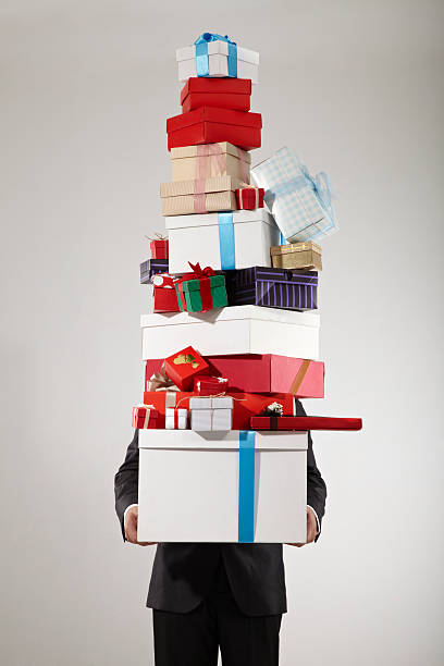businessman carrying stack of gift box - large group of objects stock photos and pictures