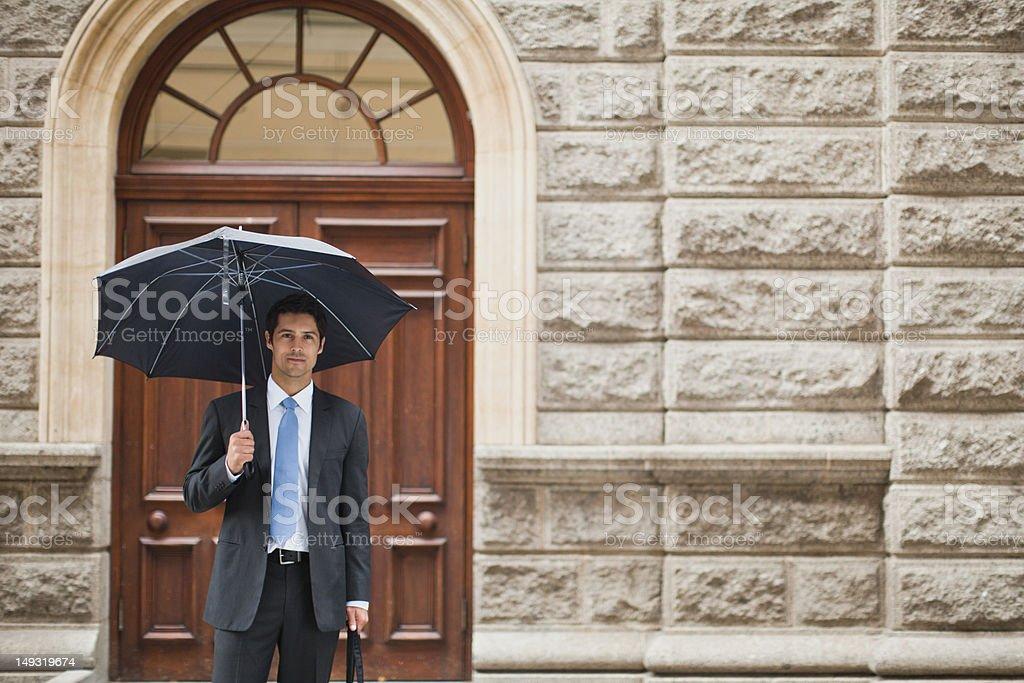 Businessman carrying umbrella on street stock photo