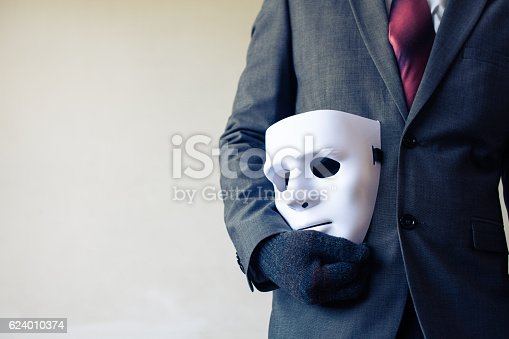 istock Businessman carrying white mask - business fraud and faking concept 624010374