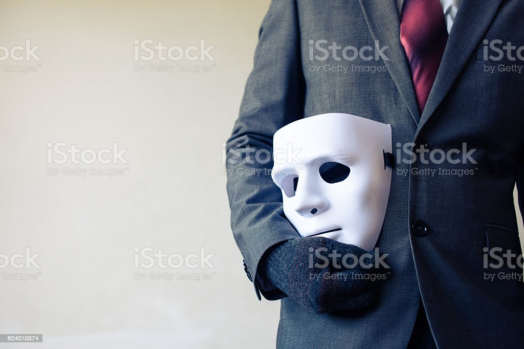 Businessman carrying white mask - business fraud and faking concept stock photo