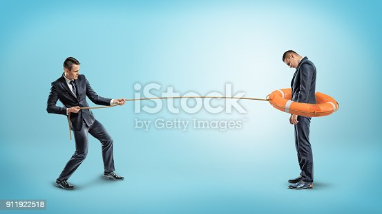 istock A businessman catches another man with an orange life buoy used as a lasso 911922518