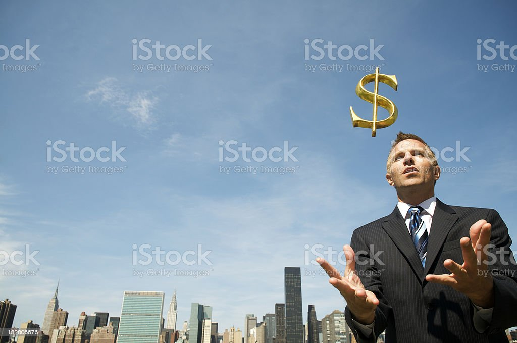 Businessman Catches Golden Dollar at City Skyline royalty-free stock photo