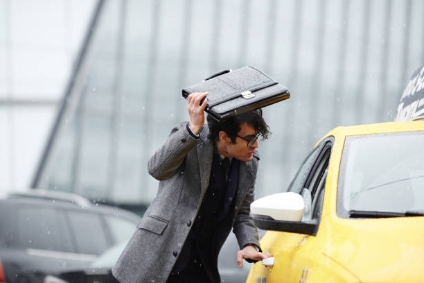 businessman catching taxi in storm - drenched stock pictures, royalty-free photos & images
