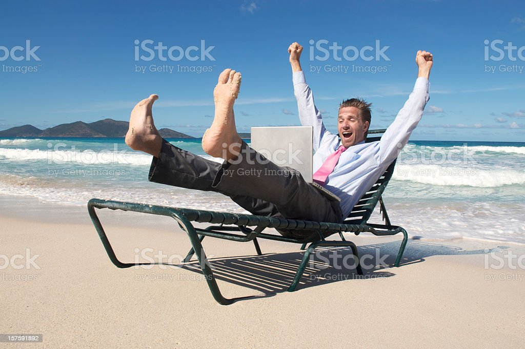 Businessman Celebrates by Sea with Laptop on Beach Chair stock photo