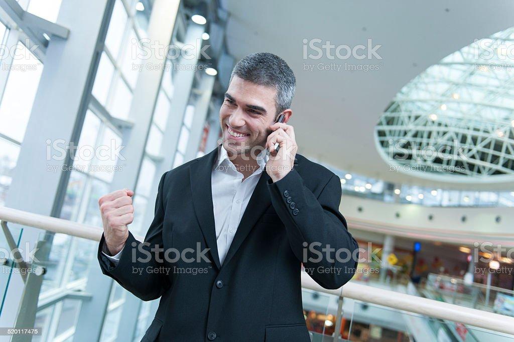 Businessman celebrates talking on mobile phone stock photo