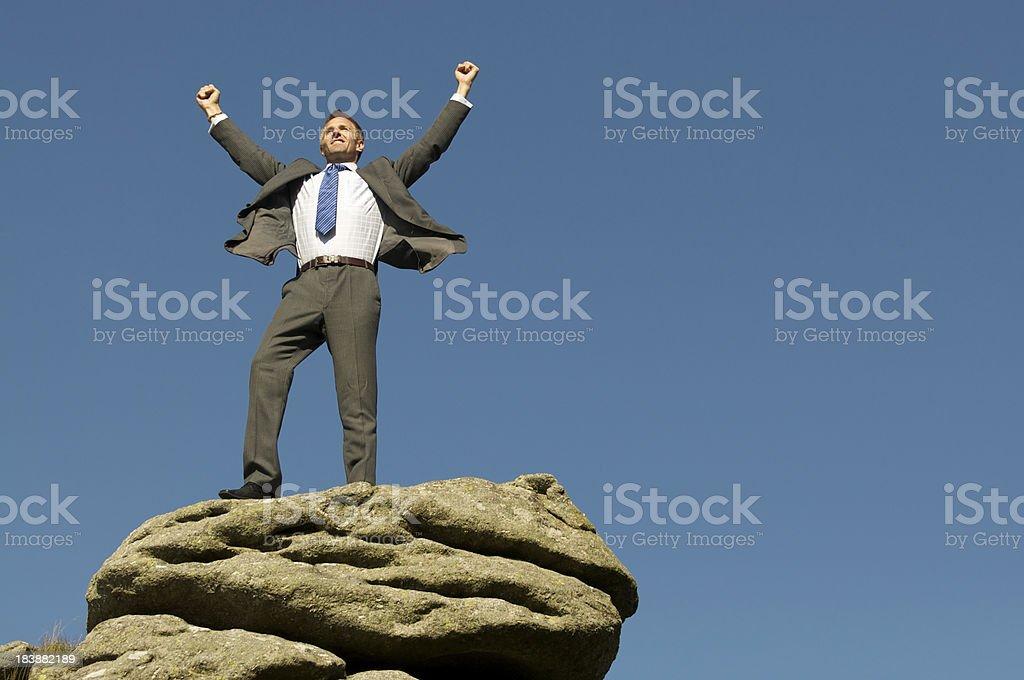 Businessman Celebrates Victory on Rocky Mountaintop stock photo