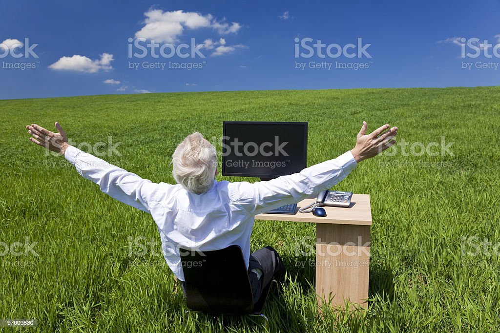 Businessman Celebrating Arms Raised At Desk In Green Field royalty-free stock photo
