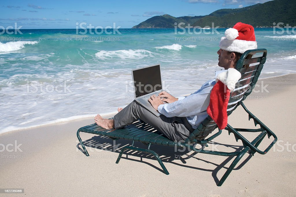 Businessman Celebrating Christmas at the Beach with Laptop royalty-free stock photo