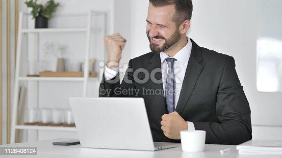 888751614 istock photo Businessman Celebrating Success, Working on Laptop 1126408124