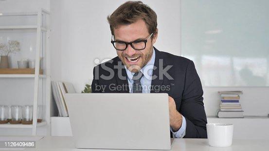 888751614 istock photo Businessman Celebrating Success, Working on Laptop 1126409486