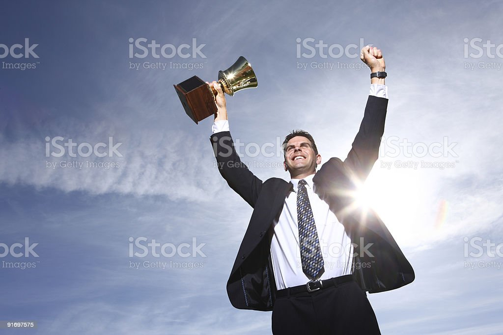 Businessman celebrating with trophy in hand stock photo