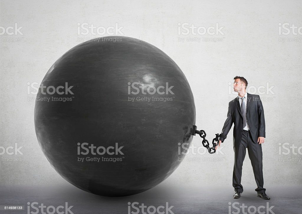 Businessman chained to a large ball stock photo