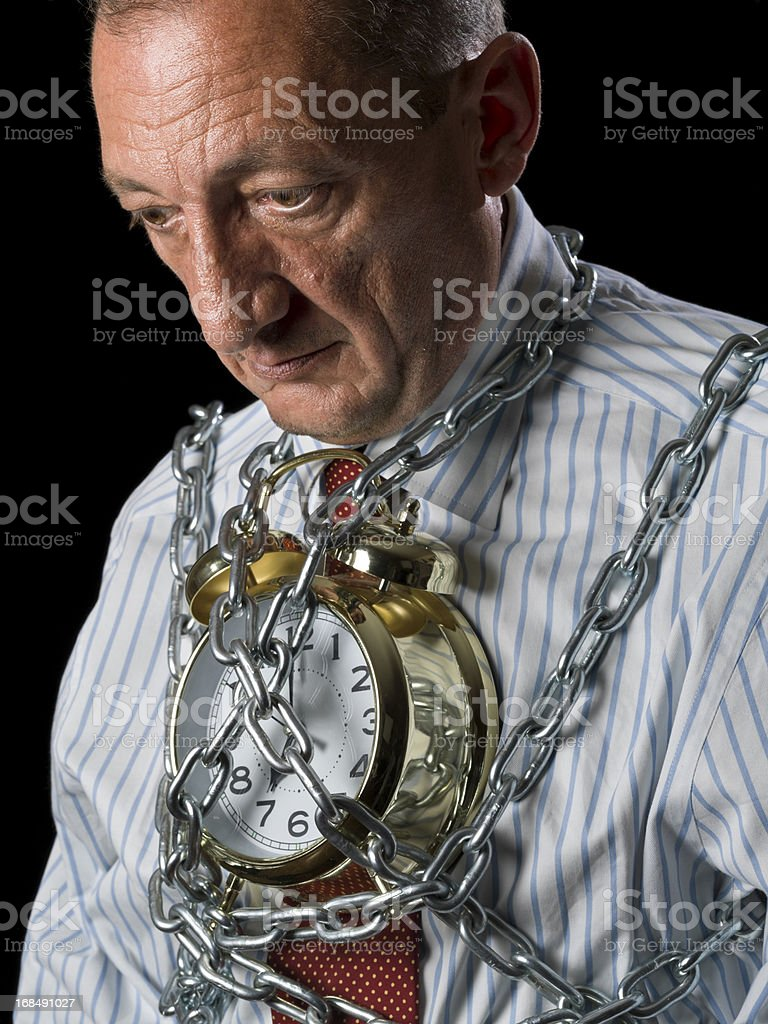 Businessman chained to the clock royalty-free stock photo