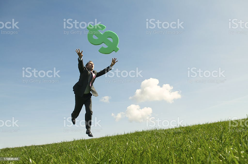 Businessman Chasing Success in Green Dollar Meadow stock photo