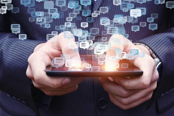 homme d'affaires chatter sur un téléphone cellulaire. - chatbot photos et images de collection