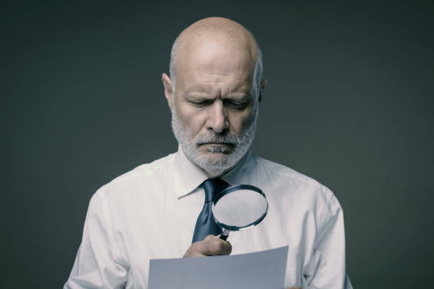 Businessman checking a document with a magnifier stock photo