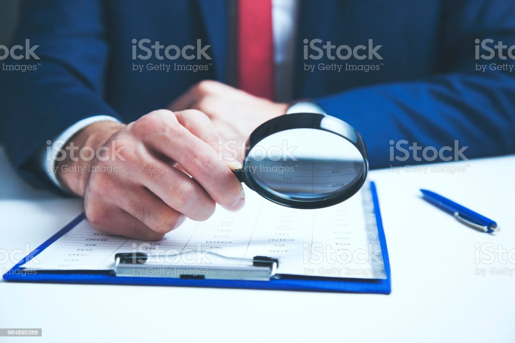 Businessman checking a document with a magnifying glass royalty-free stock photo