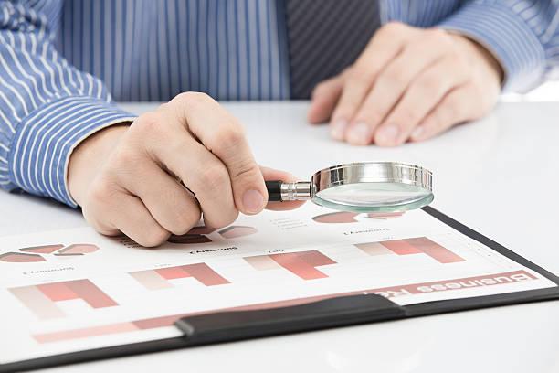 Geschäftsmann, die ein Diagramm mit einer Lupe im Büro – Foto