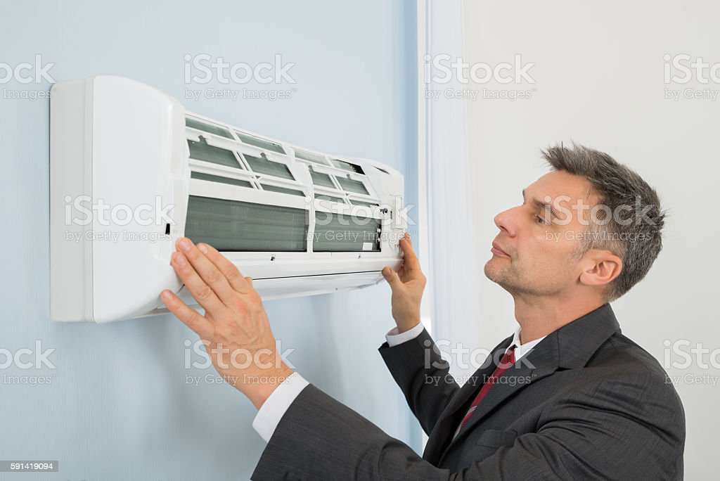 Businessman Checking Air Conditioner In Office stock photo