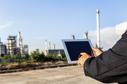 Businessman checking around oil refinery plant with clear sky