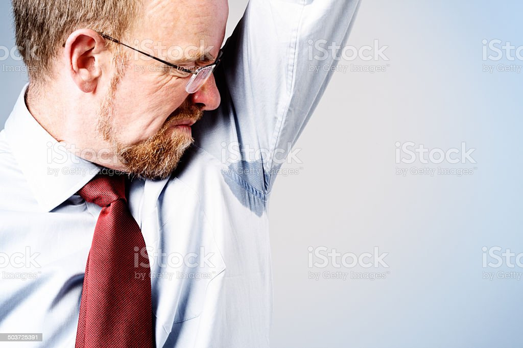Businessman checking damp armpit. Deodorant not working it seems! stock photo