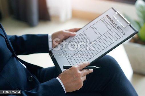 istock Businessman checking document and completing a insurance claim form at office work, insurance concept 1182775794