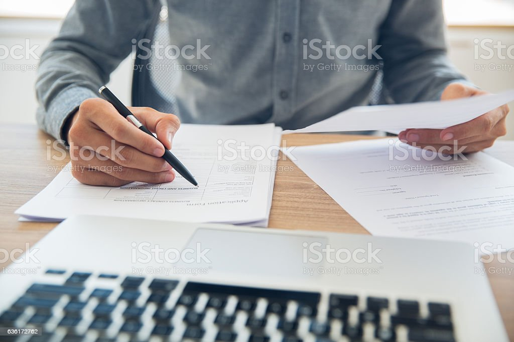 Businessman checking documents at table stock photo