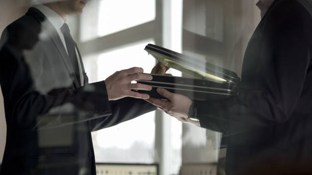 Businessman checking dollars in briefcase, kickback in illegal cooperation stock photo