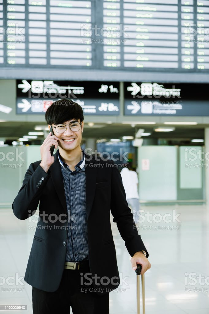 Elegant asian businessman checking email on mobile phone while...