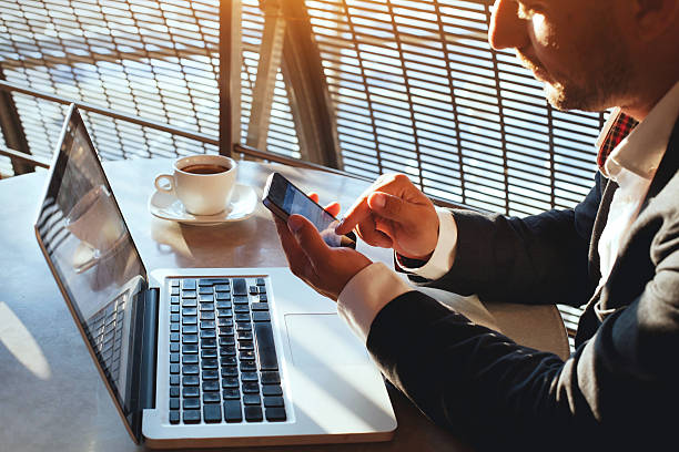 businessman checking email on smartphone business man using internet on  smart phone and laptop convenience stock pictures, royalty-free photos & images