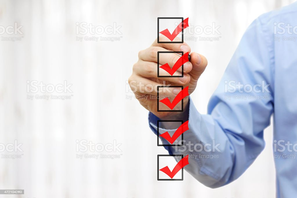 businessman checking final  mark on checklist businessman checking final  mark on checklist 2015 Stock Photo