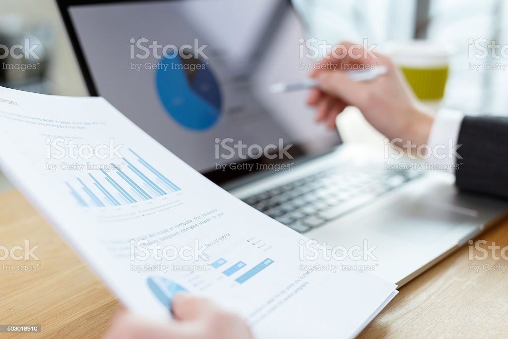 Uomo d'affari Controlla report finanziari per tavolo - foto stock