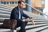 Businessman checking his mobile phone sitting on steps outdoor