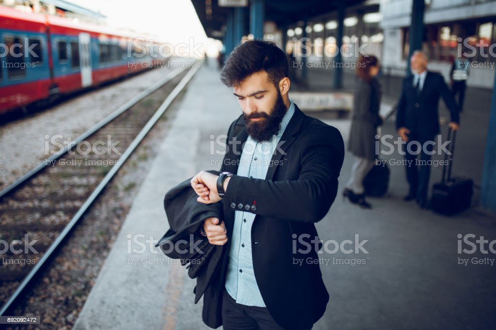 Businessman checking his watch at train station stock photo