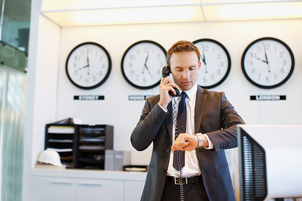 Businessman checking his watch in office stock photo