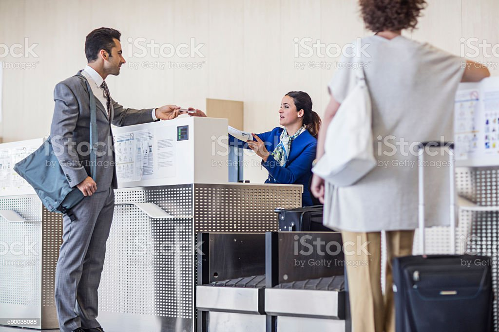 Businessman checking in at airport counter stock photo
