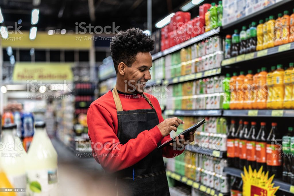 Businessman checking inventory in a digital tablet at a supermarket stock photo