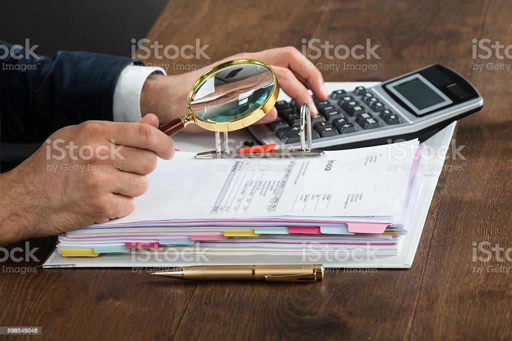 Homme vérifiant une facture avec une loupe photo libre de droits