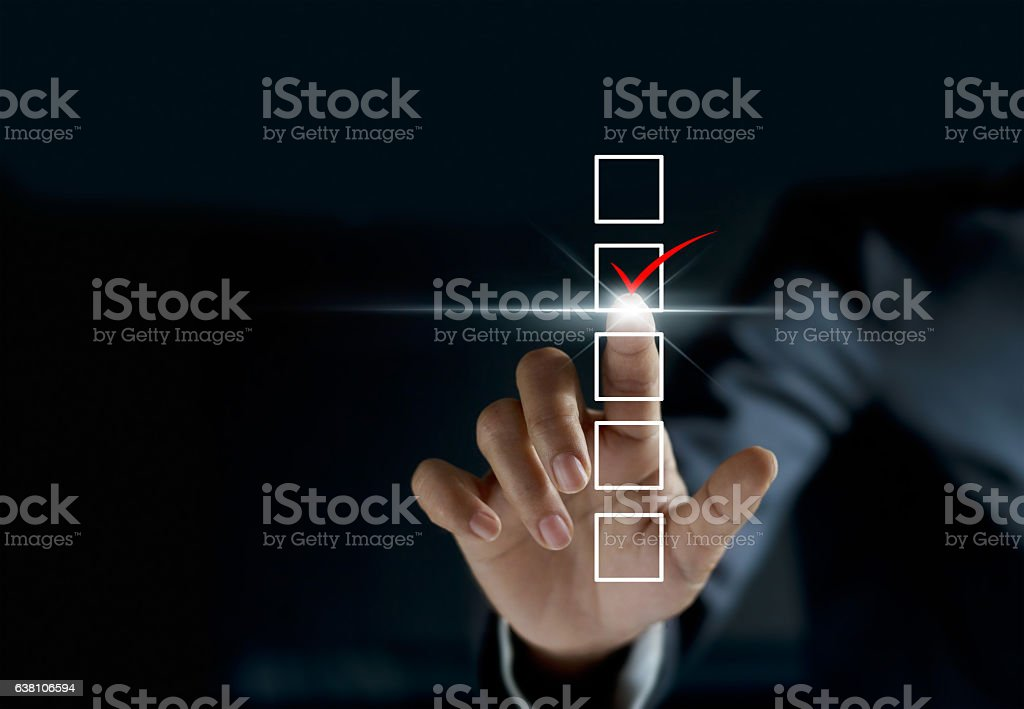 businessman checking mark on checklist with a red marker stock photo