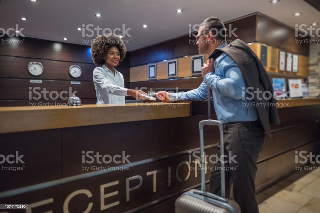 Businessman checking out at the hotel reception desk stock photo