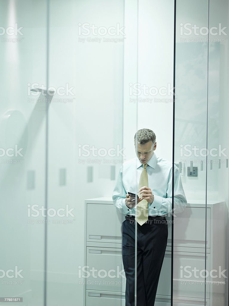 Businessman checking PDA in office stock photo