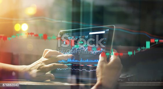 865596966istockphoto Businessman checking stock market data on tablet at night background 876883540