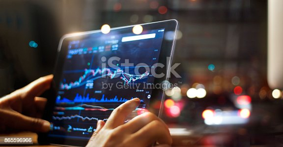 Businessman checking stock market data on tablet on night background