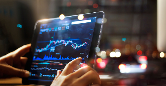 istock Businessman checking stock market data on tablet on night background 865596966